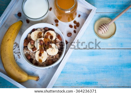 Healthy breakfast - oatmeal with bananas, raisins and honey and a glass of milk. - stock photo