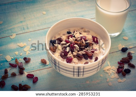 Healthy Breakfast - Oatmeal with dried fruit and glass of milk. - stock photo