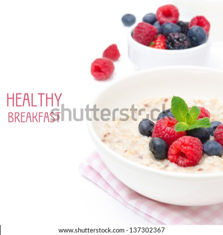 healthy breakfast - oatmeal with fresh berries in a bowl isolated on white, fresh berries in the background