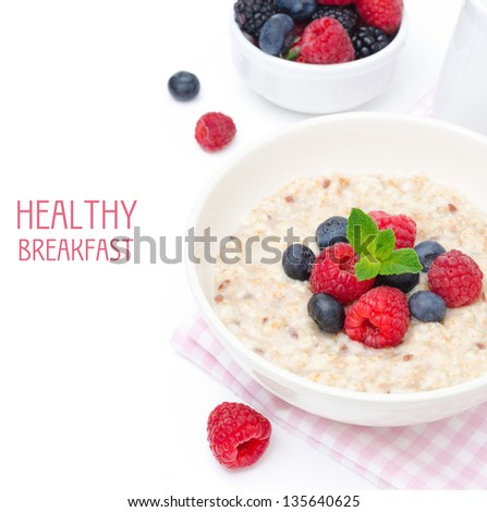 healthy breakfast - oatmeal with fresh berries in a bowl isolated on white, fresh fruit, yogurt, and milk jug in the background, top view - stock photo