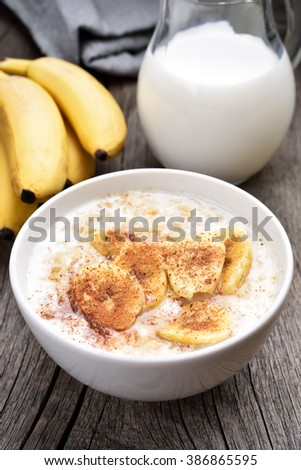 Healthy breakfast oats porridge with banana sloces and cinnamon, country style