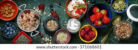 Healthy breakfast of muesli, berries with yogurt and seeds on dark background -  Healthy food, Diet, Detox, Clean Eating or Vegetarian concept. - stock photo