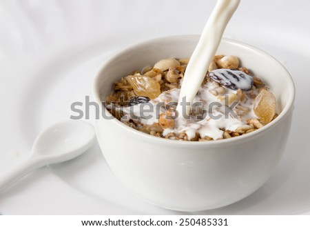 healthy Breakfast of muesli with fruits, berries and milk in a white plate close up - stock photo