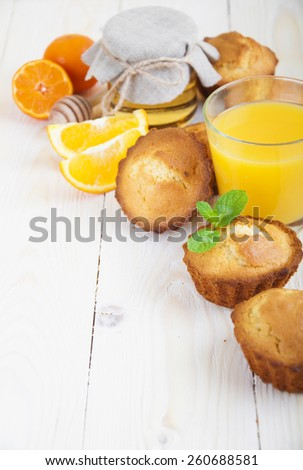 Healthy breakfast of muffins, juice, oranges and honey on wooden background - stock photo
