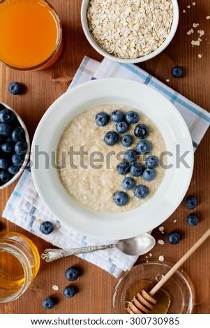 Healthy breakfast of oatmeal porridge, berries, honey and juice - stock photo