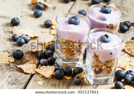 Healthy breakfast of whole grain cereal, muesli and blueberries in a glass on old wooden table, selective focus - stock photo