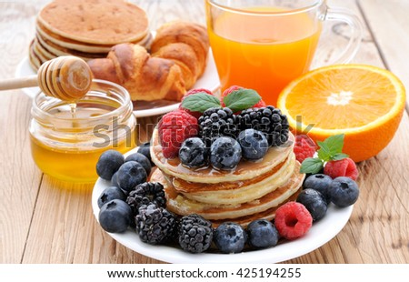Healthy Breakfast.Pancakes with berries,fresh juice, croissants and honey - stock photo