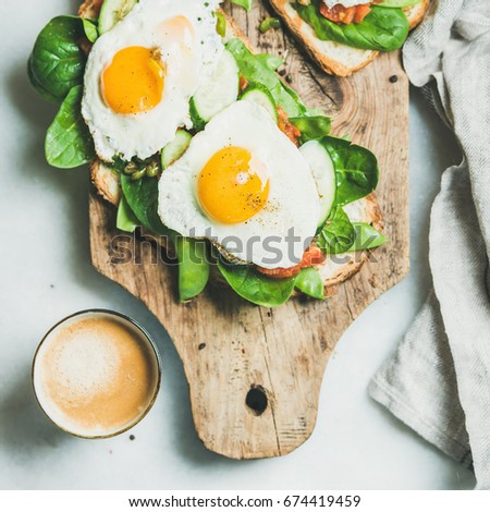 Healthy breakfast sandwiches and cup of coffee. Bread toasts with fried eggs and fresh vegetables on rustic wooden board over grey marble background, top view, square crop. Clean eating food concept