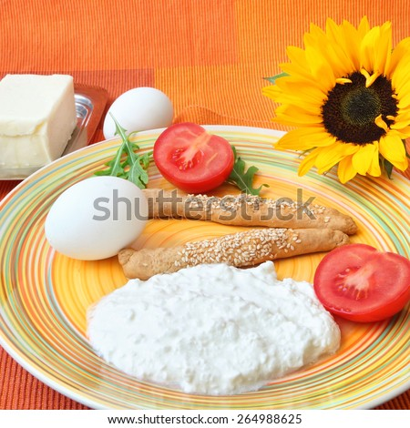 Healthy breakfast served on a colorful napkin with a sunflower - Cottage cheese, butter, boiled eggs, grain cookies, fresh tomatoes and salad leaves (rucola).  - stock photo