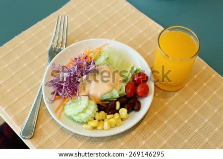 Healthy breakfast set, Fresh vegetable salad and orange juice. - stock photo
