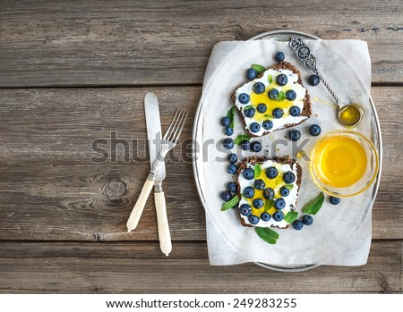 Healthy breakfast set with ricotta, fresh blueberries and honey sandwiches on whole grain bread served with mint on a silver dish over a rustic wood background with a copy space. Top view - stock photo