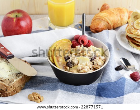 Healthy breakfast table: bowl of oatmeal porridge with caramelized apples, walnuts and raisins, pancakes with banana and coconut, orange juice, croissant and toasts with butter - stock photo