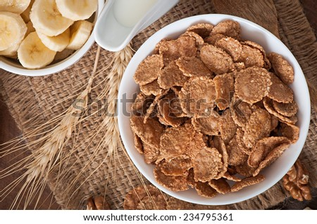 Healthy breakfast - whole grain muesli with a banana in a white bowl - stock photo