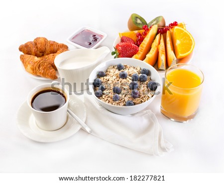 healthy breakfast with bowl of muesli, coffee, croissants, juice and fruits - stock photo