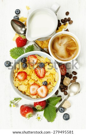 Healthy Breakfast with coffee, corn flakes, milk and berry on old wooden background. Health and diet concept - stock photo