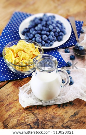 Healthy breakfast with corn flakes, berries, milk on wooden background  - stock photo