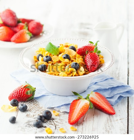 Healthy breakfast with cornflakes and fresh berries on white wooden background, selective focus