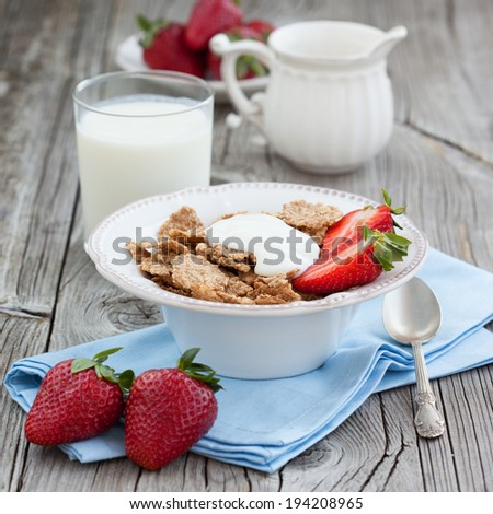 Healthy breakfast with cornflakes, milk and fresh berries on dark wooden table, selective focus - stock photo