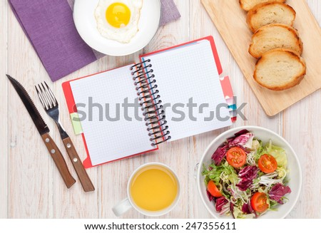 Healthy breakfast with fried egg, toasts and salad on white wooden table with notepad for copy space - stock photo