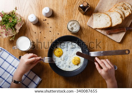Healthy breakfast with fried eggs in a frying pan on a wooden table - stock photo