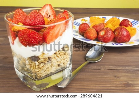 Healthy breakfast with fruit. Homemade yogurt, oatmeal with strawberries, apricots and chocolate. Sprinkled with cocoa. Decorated with a healthy breakfast.  - stock photo