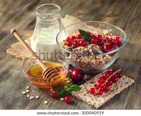 Healthy breakfast with muesli or granola, milk, fresh berries, red currant, whole-grain crispbread, honey. Rolled oats, morning cereals. - stock photo