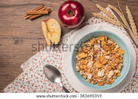 Healthy breakfast with muesli, red apple and cinnamon on rustic wooden table. Top view with copy space. - stock photo