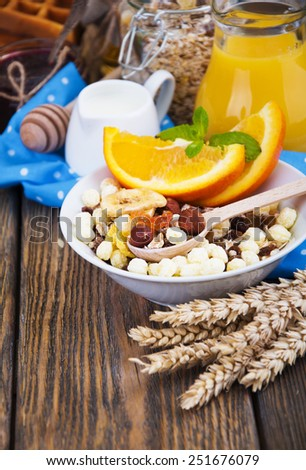 Healthy breakfast with muffins,tea,tangerines, jam and honey on a wooden background - stock photo