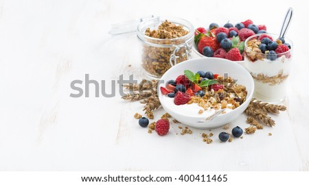 healthy breakfast with natural yogurt, muesli and berries and white background, horizontal