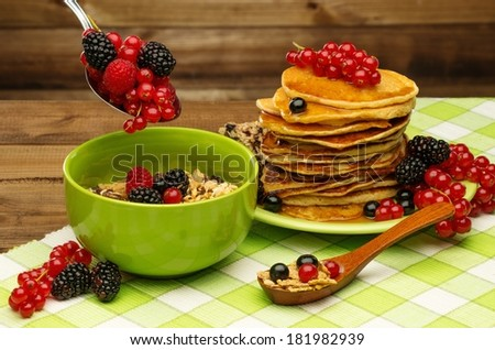 Healthy breakfast with pancakes, fresh berries and muesli on tablecloth in rural interior