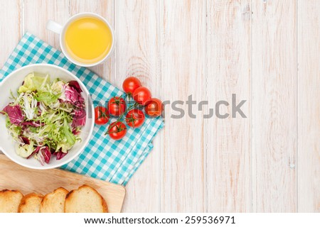 Healthy breakfast with salad, tomatoes and toasts on white wooden table. Top view with copy space - stock photo
