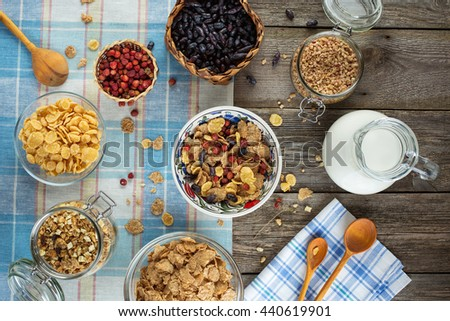 Healthy breakfast with wild strawberries, honeysuckle, cereals, muesli and milk on a laid table. Rustic style, top view