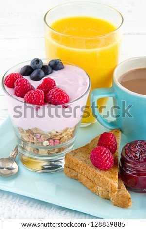 Healthy breakfast with yoghurt, berries, juice, toast and coffee, on white wooden background - stock photo