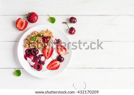 Healthy breakfast with yogurt, muesli and berries. Summer berry yogurt, top view, flat lay - stock photo