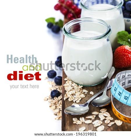 Healthy breakfast - yogurt, muesli, berries and measurement tape - health and diet concept - stock photo