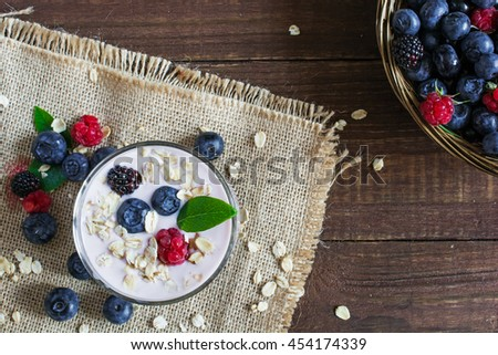 healthy breakfast. Yogurt with granola and berries in a glass on rustic wooden table with ripe berries around and in wicker bowl. top view - stock photo