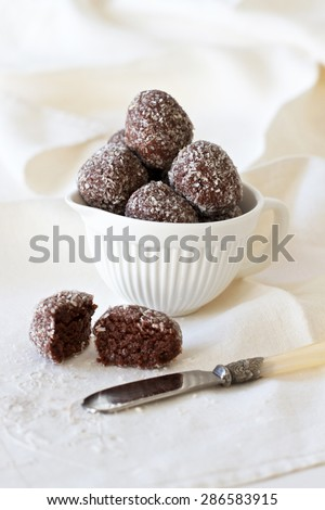 Healthy cacao protein balls made with dates and coconut in a white bowl