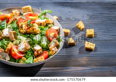 Healthy Caesar salad made of fresh vegetables on blue table - stock photo