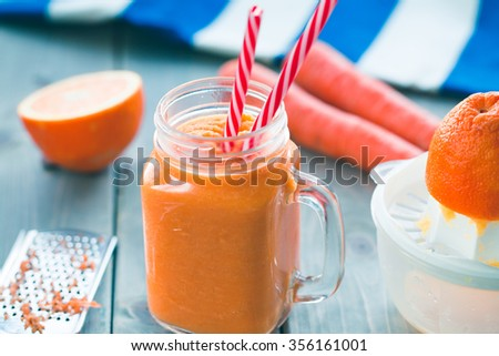 Healthy carrot orange smoothie in a jar with tube wooden background.  Selective focus - stock photo