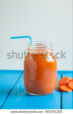 Healthy carrot  smoothie in a jar on blue wooden background. Vegetable drink.