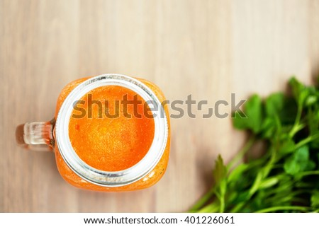 Healthy carrot smoothie in a jar on wooden background - stock photo