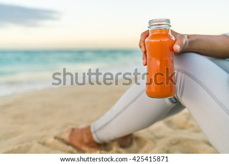 Healthy carrot vegetable juice detox cleanse woman drinking smoothie for weight loss diet at beach sunset. Closeup of fresh orange glass bottle. Juicing trend, raw, organic and cold-pressed. - stock photo