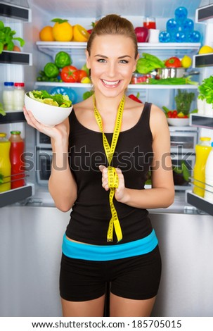 Healthy cheerful girl holding in hand bowl with fresh tasty green salad, dietitian recommending eating vegetables, healthy organic nutrition concept - stock photo