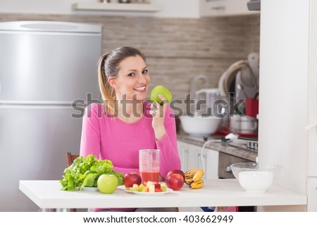 Healthy cheerful woman eating and apple an sitting in kitchen. - stock photo