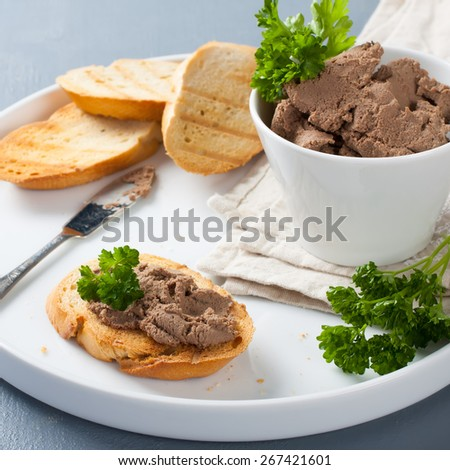 Healthy chicken liver pate with parsley in bawl and on bread,  selective focus - stock photo