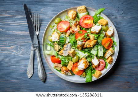 Healthy chicken salad with fresh vegetables on blue table - stock photo