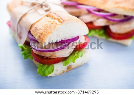 Healthy chicken sandwiches with salad, tomato and onion on blue wooden background close up. - stock photo