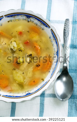 Healthy chicken soup with spoon on kitchen towel. Top view. - stock photo