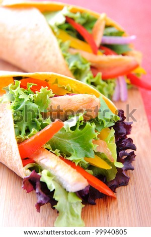 Healthy chicken strips and fresh salad wrapped in a corn tortilla - stock photo