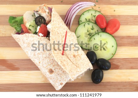 Healthy chicken wrap greek style with fresh vegetables, black olives, feta cheese and herbs - stock photo